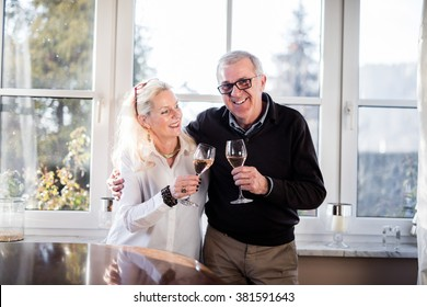 Older good looking and handsome couple drinking champagne at home and clinking glasses