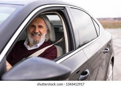 Older handsome gentleman is driving his car and looking trough the window