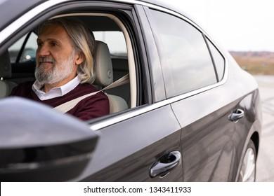 Older handsome man is enjoying driving his car