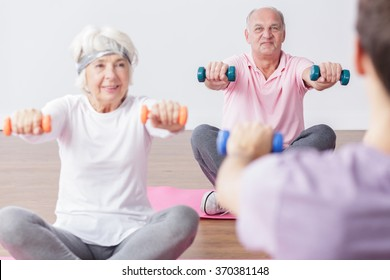 Older happy man and woman exercising with dumbbells