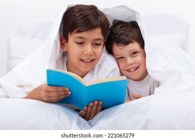 Older kid reading to his little brother - laying in bed