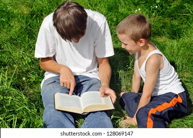 Older and Little Brothers reads a Book in the Summer Park