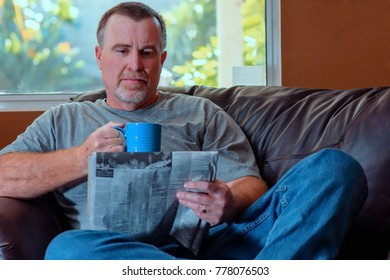 Older male enjoys paper and relaxes with cup of coffee