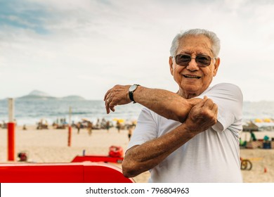 Older man (80-85) stretching his triceps at beach in Ipanema, Rio de Janeiro, Brazil