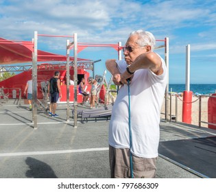 Older man (80-89) exercsing with a stretch cord at open air gym in Ipanema Beach, Rio de Janeiro, Brazil