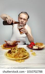 Older man in a-shirt eating lot of junk food.