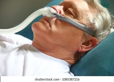 Older man with breathing apparatus for sleep apnea