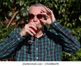 Older man in bright sunlight wearing sunglassses and drinking red wine