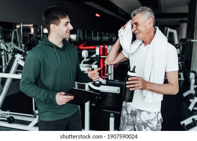 An older man communicates with his coach, they stand in the middle of a modern gym. Sports, health. Rehabilitation specialist, coach.