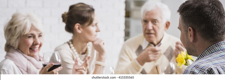 Older man discussing with his adult kids during family supper. Older smiling mother drinking red wine