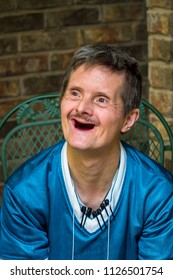 An older man with Downs Syndrome gives a huge smile.  The delight on his face shows off the fact that he has no more teeth.  The markers clipped to his shirt show that he collects pens.