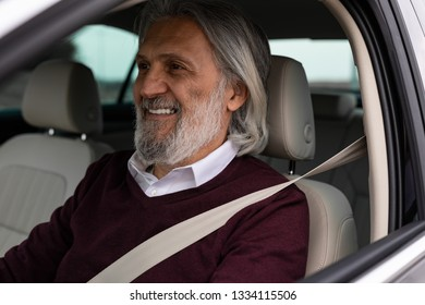 Older man driving his car and smiling