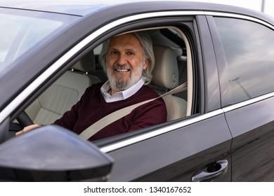 Older man enjoys driving his car