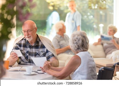 Older man in glasses sitting with his female friend by the table and watching photos