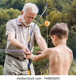 Older man (grandfather) showing a child (nephew) how to place the arrow in the bow