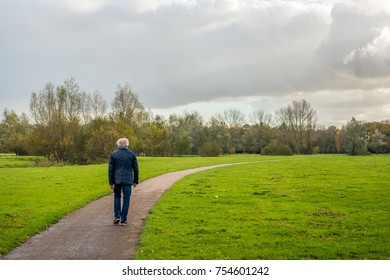 Older man with gray hair walks over a curved footpath through the park on a cloudy day in the fall season.
