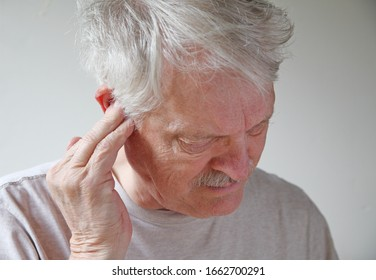 Older man with a hand to his ear has a possible infection