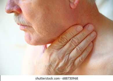 Older man with his hand against his throat, natural light