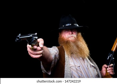 Older man holds his pistol up to shoot while in his other hand has his rifle ready