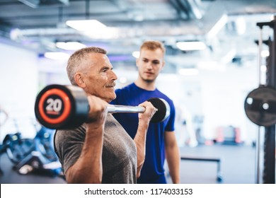 Older man lifting weights, supervised by gym assistant. Sporty lifestyle of elderly people.