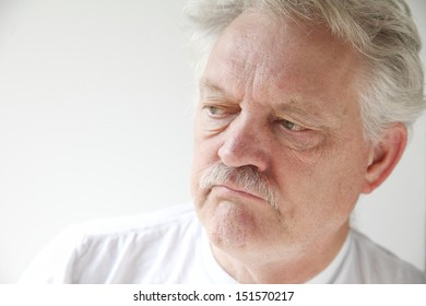 older man with a negative, disgruntled expression