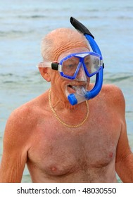 Older man on a beach wearing blue snorkel and dive mask