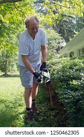An older man operating electronic pruning shears to prune a long hedge in summertime