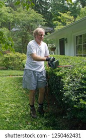 An older man outdoors using electronic pruning shears to prune a long hedge in summertime