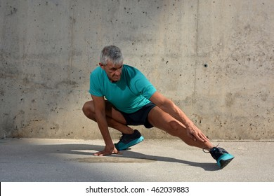 Older man practicing stretching on the street.