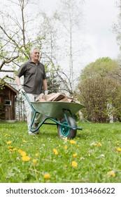 Older man pushing wheelbarrow