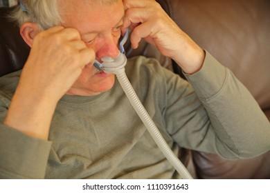 Older man puts on an apparatus for sleep apnea