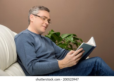 older man reading book on sofa. man sitting on couch and holding book