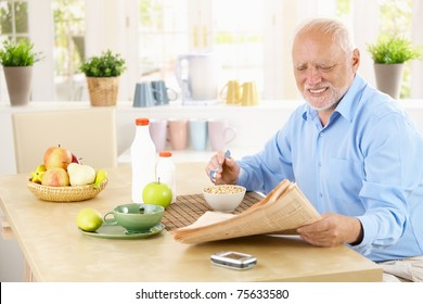 Older man reading newspaper in kitchen while having cereal breakfast.?