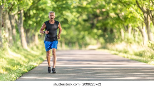 Older man runs uphill in the nature during a summer day keeping his fitness level high.