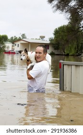 An older man saving his beloved dog during a flood and showing flooded items in the background.