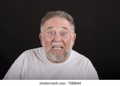 An older man showing shock or surprise against a black background