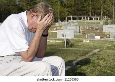 An older man sitting in the cemetery.