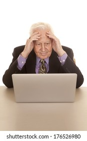 An older man sitting at a laptop computer with his hands on his head.