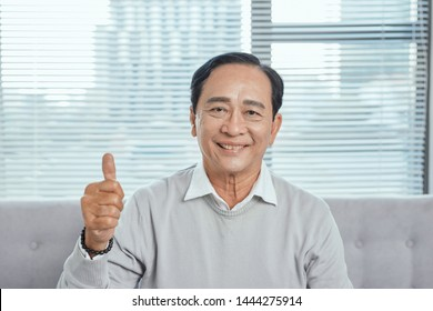 Older man sitting on couch giving thumb up while playing computer game, looking at camera, smiling.?