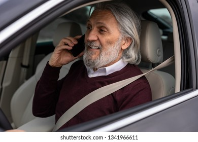 Older man is speaking on his phone while driving the car