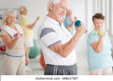 Older man in sportswear training together with his friends using dumbbells