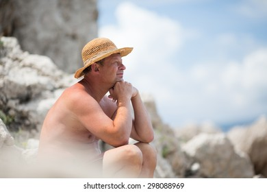 Older Man with straw hat sitting on the reef and looking away.