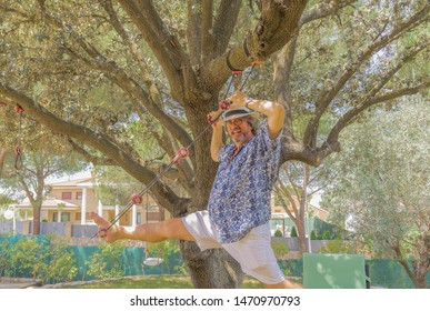 An older man stretching his feet on a sunny day in the park - Man with beard and white hat - Colorful portrait