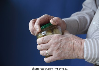 an older man struggles to open a jar of pickles