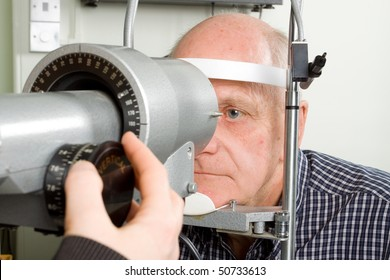 An older man taking an eye test examination at an opticians clinic