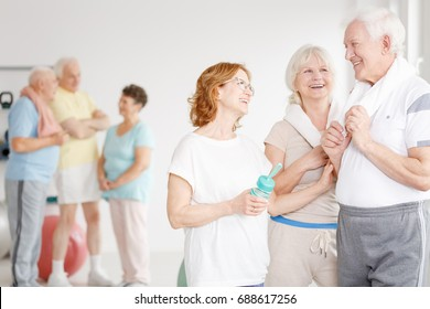 Older man talking to senior woman before group training in spacious gym room