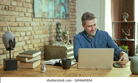 Older man tele working with laptop computer at home office in living room, thinking, looking busy.