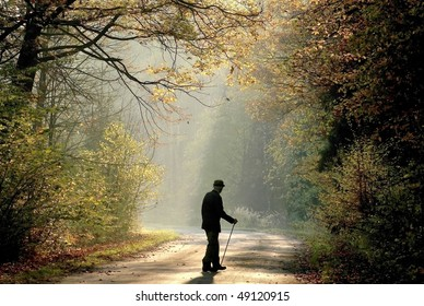 Older man through the country road in autumn forest in the light of the rising sun.