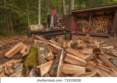 Older man using log splitter near a wood shed