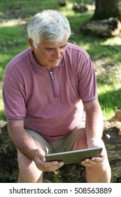 Older man using tablet in the park or garden.